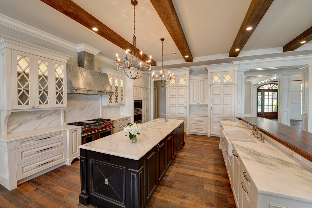 Large kitchen with white cupboards and countertops, with dark accented island