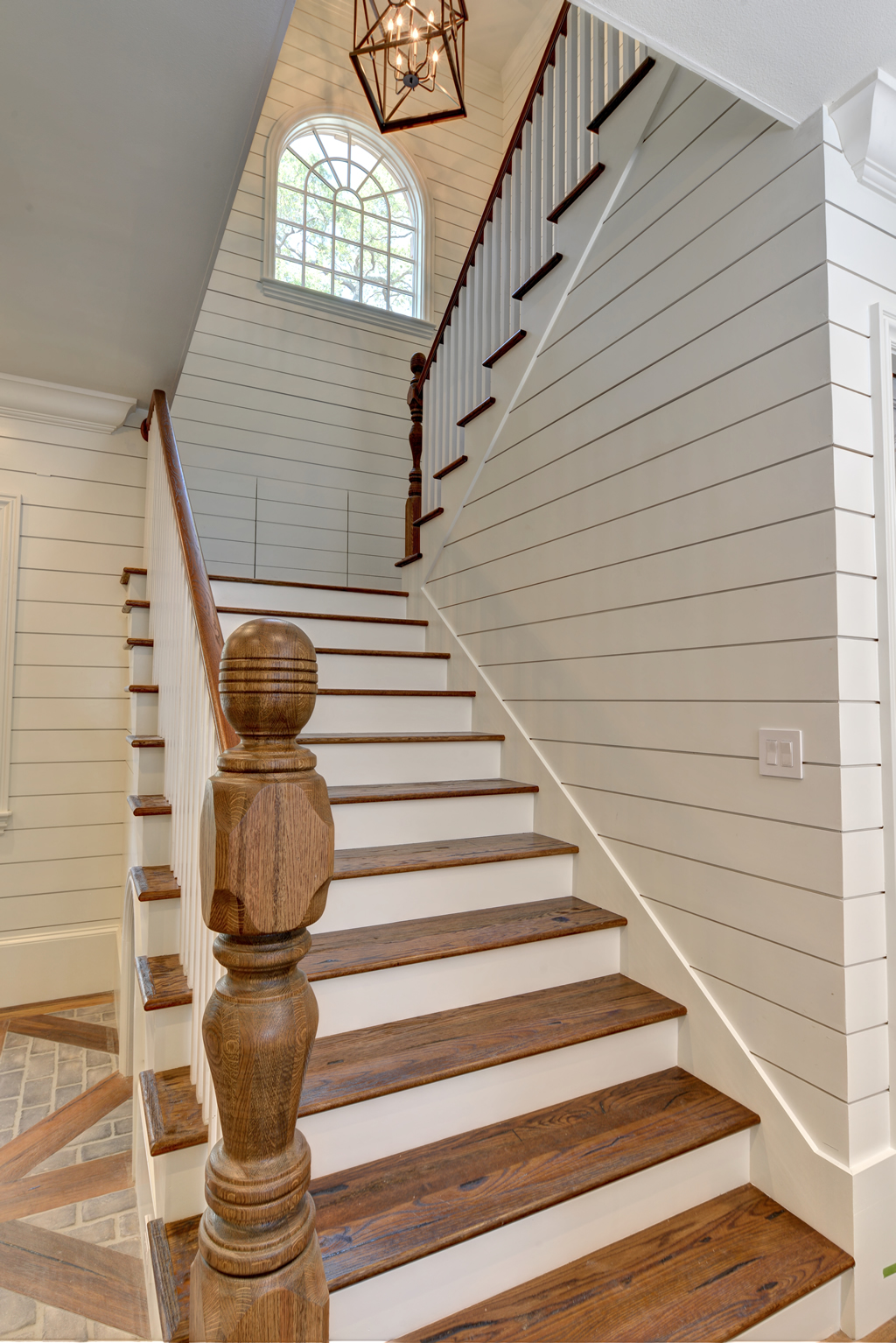 Staircase with white paneled walls and wooden accents