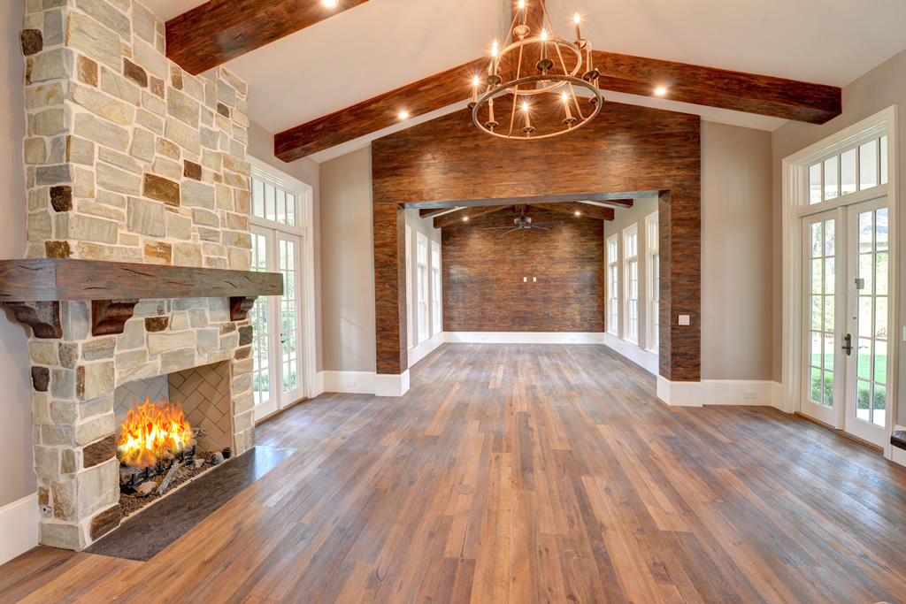 Interior of house with woods floor, wood ceiling beams, and stone fireplace