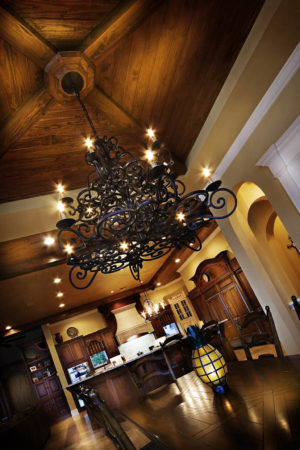 View of dining room and kitchen with dark wood pieces and stylized chandeliers