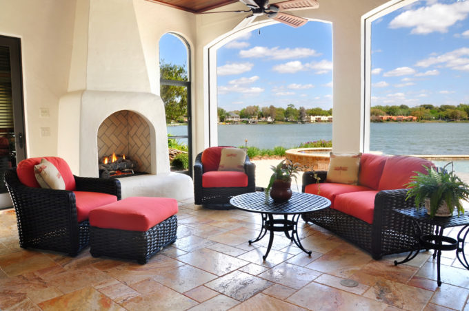 Tiled outdoor patio with fireplace with water view