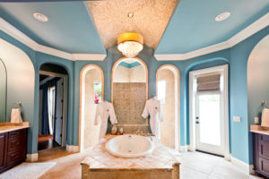 Chic, blue master bathroom with jacuzzi tub and chandelier