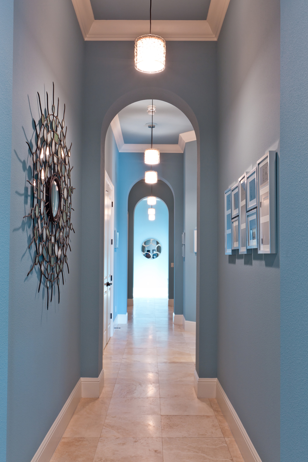 Hallway with light blue walls and tiled floors