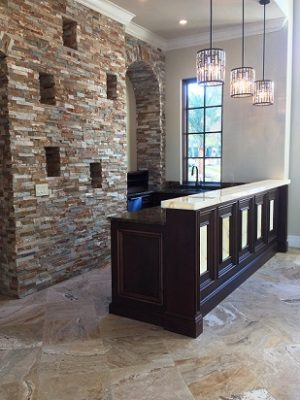 Exposed stone wall and dark wood bar with white countertop