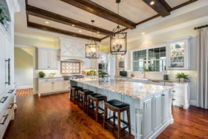 Kitchen with white cabinets, large island, and wood ceiling beams