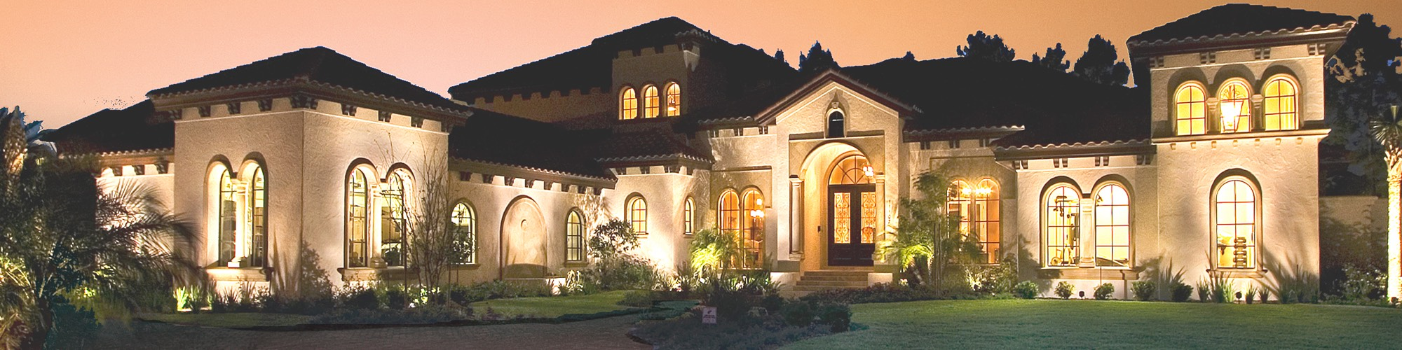 Street view of large Florida style home lit up at dusk