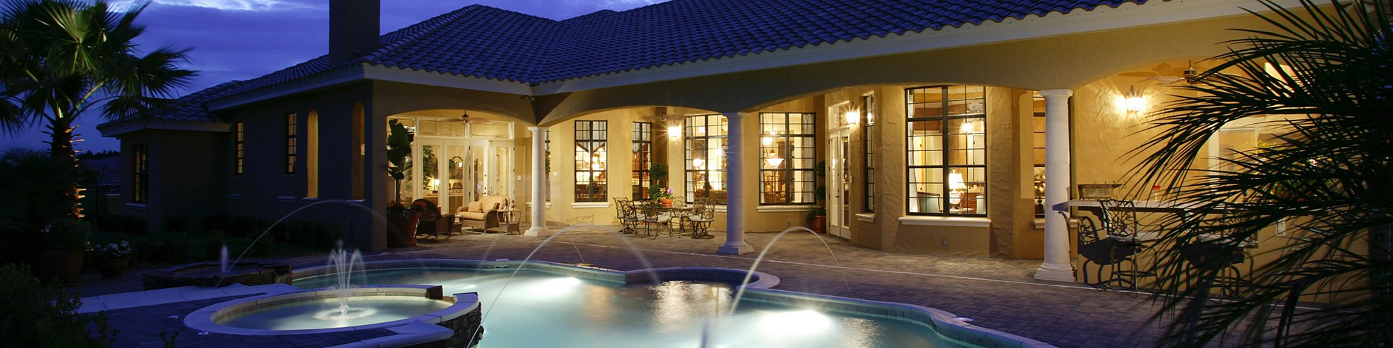View of pool, spa, and rear of home lit up at night