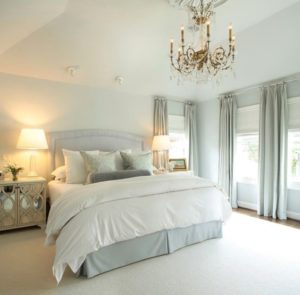 White and grey decorated master bedroom with chandelier