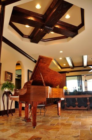 Piano on tiled floor with stylized dark wooden beams on ceiling