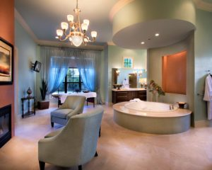 Luxurious bathroom with jacuzzi tub and sitting area with fireplace