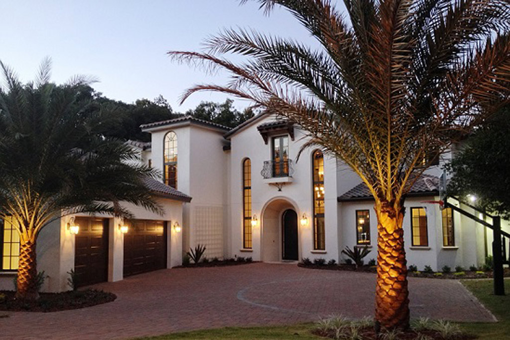 Front of Florida style house surrounded by palm trees