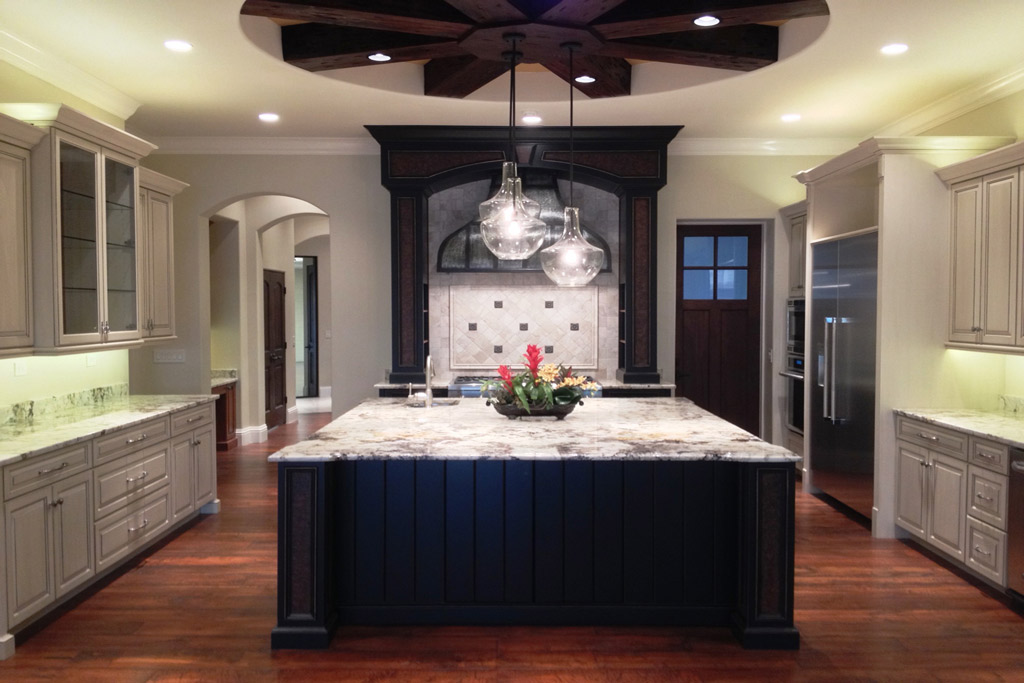 Kitchen with large square island, grey cabinets, and dark wooden accents