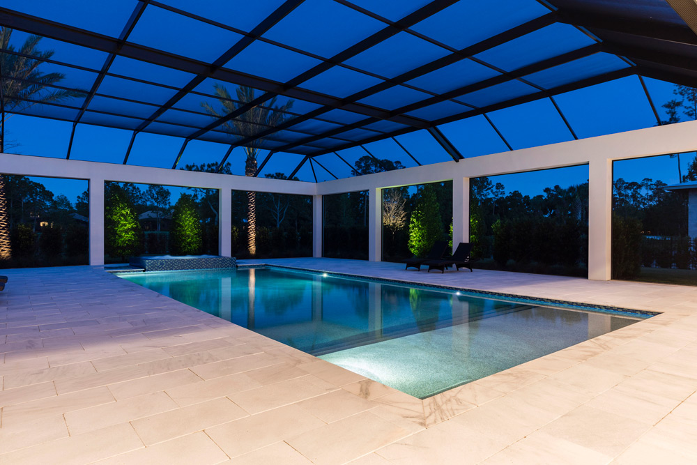 In ground pool in a lanai at twilight
